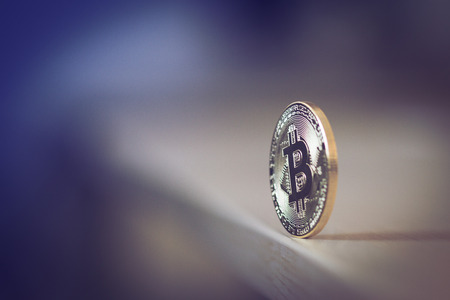 side view with selective focus of one bitcoin standing in equilibrium on edge of a wooden table Stock Photo