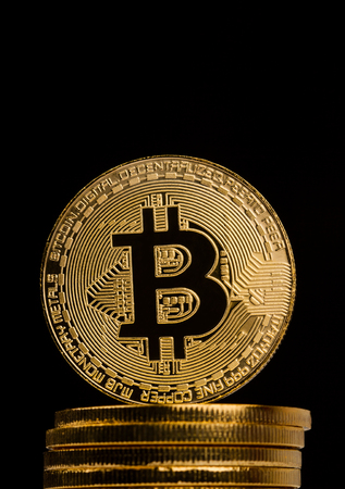 vertical front view closeup of golden bitcoin on pile of metallic coins on dark background