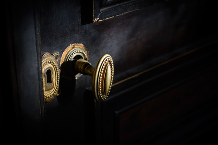 side view detail of vintage antique golden door know with metallic carvings and keyhole on dark background natural lightning Stock Photo