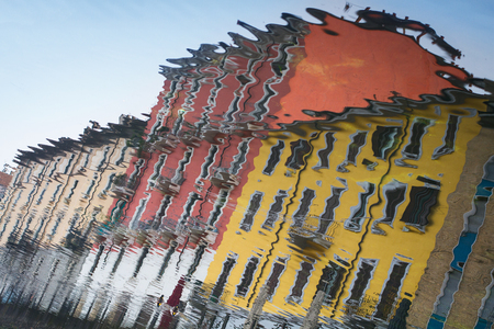 closeup reflection of colorful historical buildings in the water of Navigli Milan city canal with blue sky above