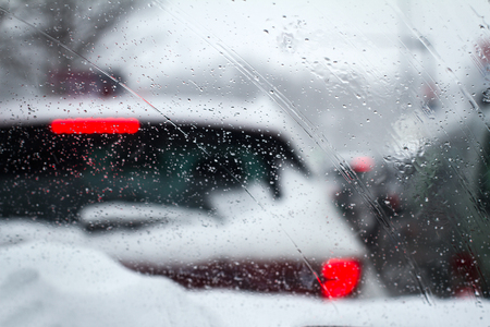 closeup of snowflakes and drizzle on windshield car driving through heavy winter city highway traffic with rear red lights of cars in front