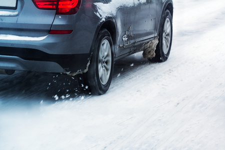 closeup rear view of a car dark color wheel tire going through snow on a city road traffic with motion blur Stock Photo