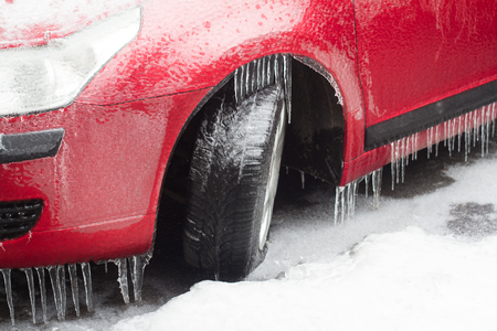 side view closeup of red frozen car with freezing rain icicles hanging on tires stopped in a parking lot covered in snow winter time