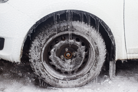side view closeup of white frozen car with freezing rain icicles hanging on tires stopped in a parking lot covered in snow winter time Stockfoto