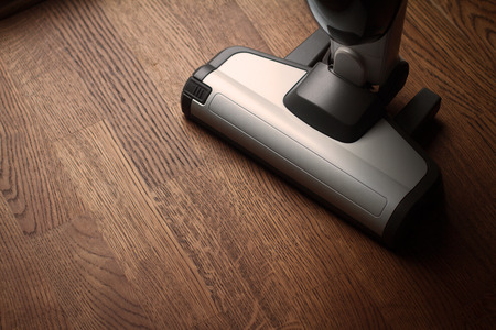 top view of white cordless vacuum cleaner head on wooden brown parquet floor in natural light with copyspace Imagens - 124626782