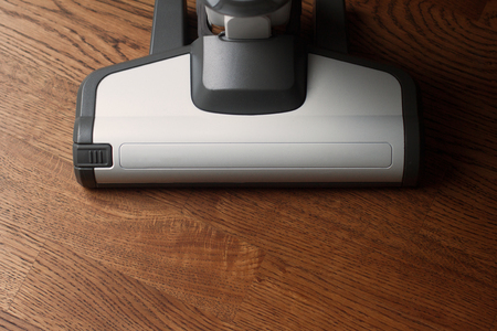 top view of white cordless vacuum cleaner head on wooden brown parquet floor in natural light with copyspace Imagens - 124626783