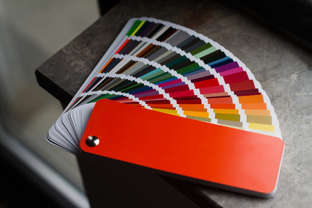 top view of multicolor color paper sampler open on dark marble window sill in natural light Stok Fotoğraf