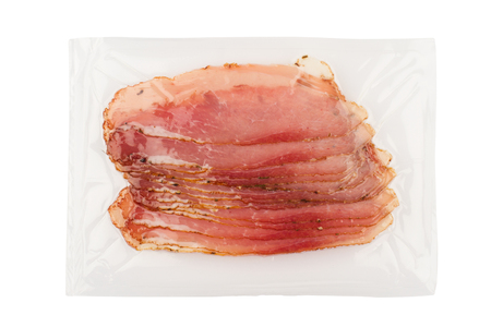 top view of slices of smoked pork loin ham in transparent plastic packaging isolated on white background