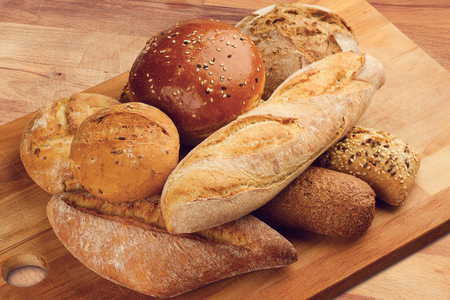 side view of different types of bread piled up on wooden kitchen cutting board