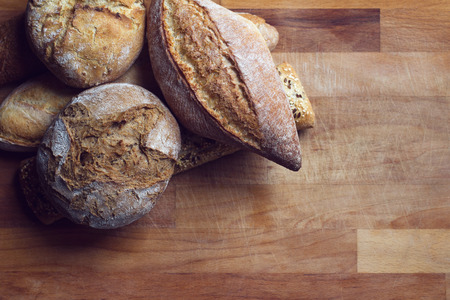 top view of different types of bread on wooden kitchen cutting board in natural light copyspace available