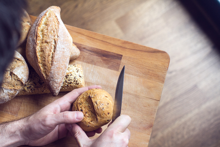 top view closeup of Caucasian male hands cutting a bread roll with knife with kitchen woodboard in the background natural light 写真素材