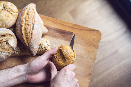 top view closeup of Caucasian male hands cutting a bread roll with knife with kitchen woodboard in the background natural light Stok Fotoğraf