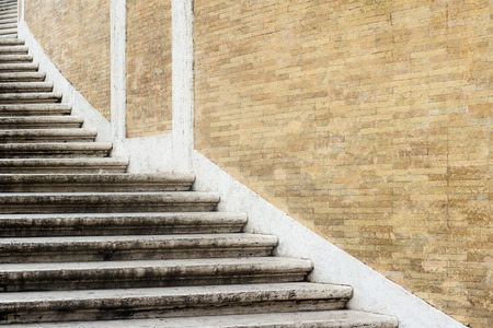 perspective view closeup pattern of wide stone spiraling classic stairs near a light brown brick wall copyspace available