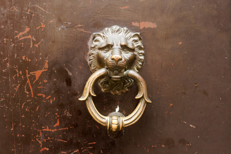 horizontal front view closeup on vintage lion head golden door knob with knocking ring on brown wooden background