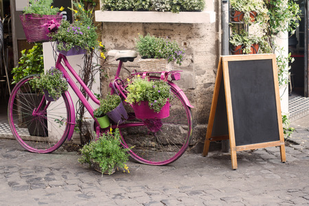 front view closeup of sidewalk retro street bistro store front with pink decorative bicycle and flowers next to empty menu chalk board 写真素材