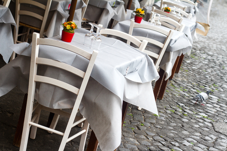 perspective view closeup of traditional Italian street  restaurant terrace with white tables and chairs on old sidewalk