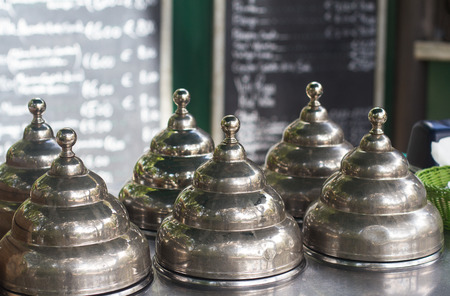 front view closeup of metallic chrome icecream vintage retro lid covers on the terrace of a street cafeteria