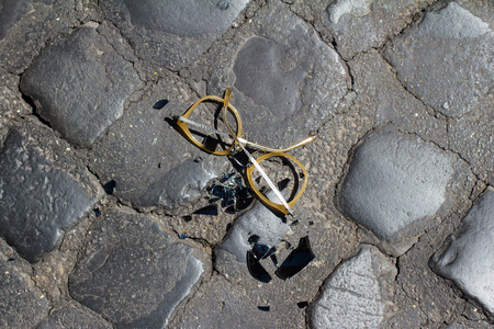 top view closeup of smashed sunglasses near black shattered glass on street stone pavement background Stok Fotoğraf