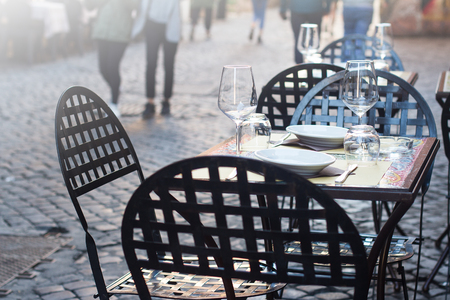 perspective view closeup of traditional Italian street  restaurant terrace with black metallic iron tables and chairs on old sidewalk with people passing by