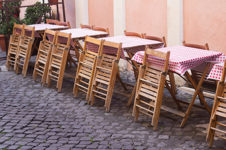 perspective view closeup of traditional Italian street  restaurant terrace with tables covered in checkered cloth and wooden chairs on old sidewalk Stok Fotoğraf