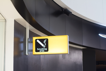 front view closeup of yellow smoking sign area signage in a business building interior