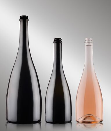 front view closeup of three champagne bottles of different sizes blank with no label two black and one rose on grey background