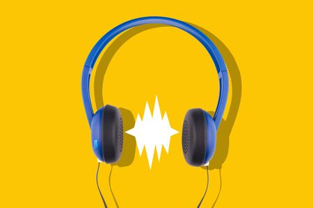 front view closeup of black and blue headphones isolated on yellow background with empty comic sound speech bubble