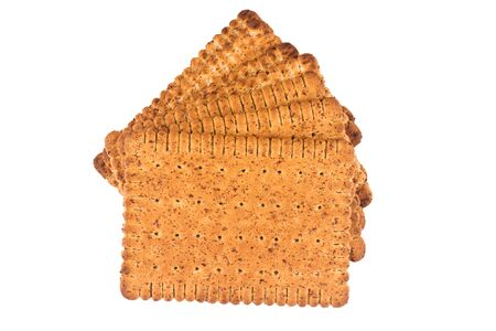 closeup of stack of square shaped wholegrain brown biscuit isolated on white