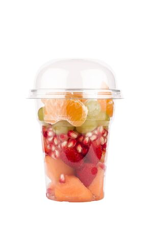 front view closeup of transparent plastic takeaway can container dome lid with a mix of many assorted fresh fruits isolated on white background Stockfoto