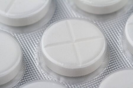 macro closeup of one medical white round pill protected in plastic capsule with plus sign on silver pharmaceutical packaging blister