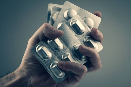 closeup of Caucasian male hand holding many different pill blister silver pharmaceutical packaging foils against grey background