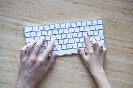 top view of Caucasian adult father and child daughter or son hands using the computer white keyboard together on wooden desk background copyspace available