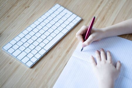 perspective view hand of Caucasian little girl writing with red pen in white notebook on light colored wooden desk with white computer keyboard in front copyspace available