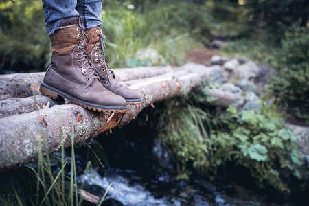 perspective view closeup of woman with brown tall leather hiking boots and grey jeans standing on a wooden trunk tree bridge over a mountain water stream in the forest Imagens
