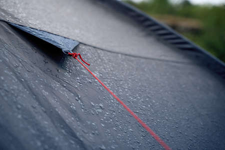 closeup detail perspective view of anchoring red rope on dark blue outdoor waterproof tent covered in rain drops Stock fotó - 153224103