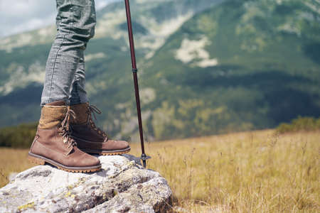 closeup detail of woman with brown leather boots and hiking stick standing on a rock with mountains in the background Imagens