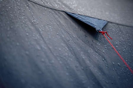 closeup detail perspective view of anchoring red rope on dark blue outdoor waterproof tent covered in rain drops Stock fotó