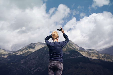 rear view portrait of Caucasian blonde woman arranging her hair tying in a bun in front of a mountain range with high peaks and blue sky with dramatic clouds Imagens