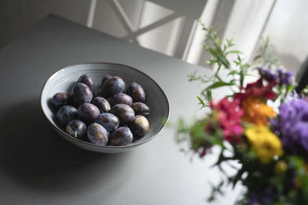 perspective top view of fresh ripe plum fruits in vintage elegant grey bowl on table indoor minimalistic setup with natural light and colorful flowers in the corner Imagens