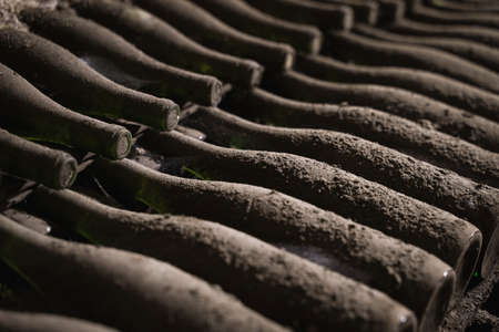 perspective view closeup of stacked aged wine bottles ancient collection covered with soft black mold and spiderweb in vintage wine cellar