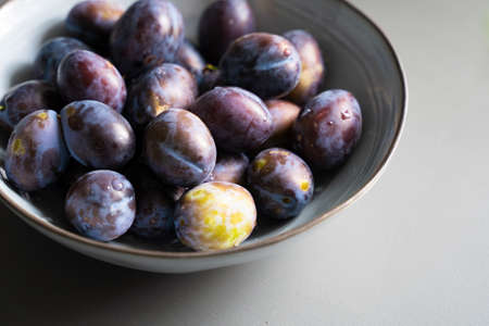 perspective top view of fresh ripe plum fruits in vintage elegant grey bowl on table indoor minimalistic setup with natural light