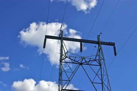 lines: A view of power lines and tower against a bright blue sky. Stock Photo
