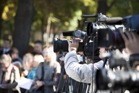 cameraman: cameraman covering an event with a video camera