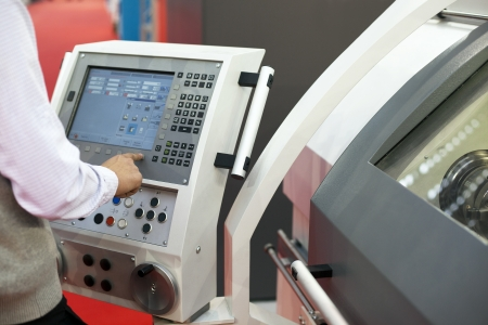 automated tooling: man working at programmable machine Stock Photo