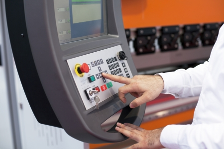 automated tooling: hand on the control panel of a programmable machine