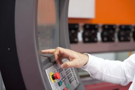 tablero de control: mano en el panel de control de una m�quina programable