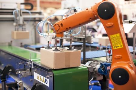 ingenieria industrial: l�nea de envasado con el brazo rob�tico en el trabajo