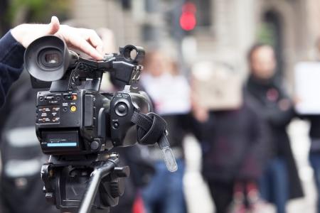 reportero: cubriendo un evento usando la c�mara de v�deo Foto de archivo
