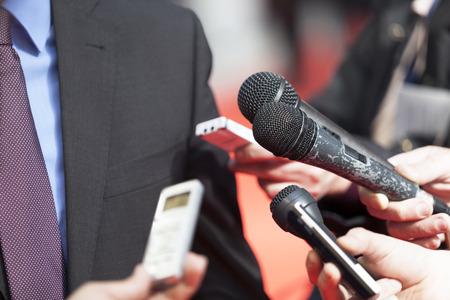 hablar en publico: Un periodista está haciendo una entrevista con un micrófono Foto de archivo