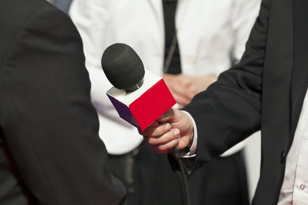 A journalist is making a interview with a microphone photo